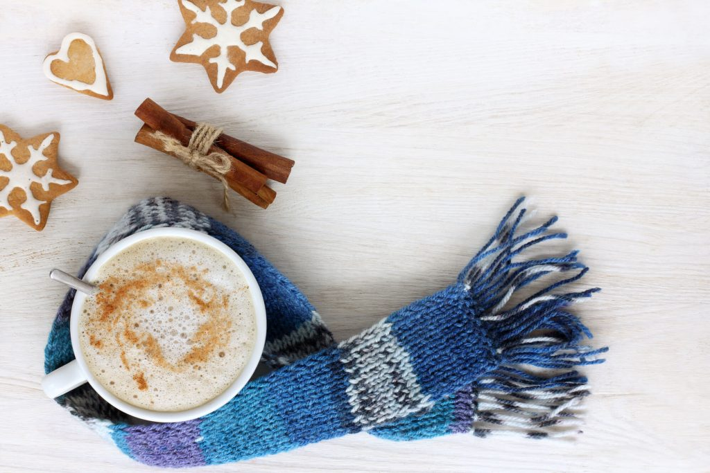 White mug of cinnamon vanilla milk tea with blue knitted scarf, cinnamon sticks and cookies.
