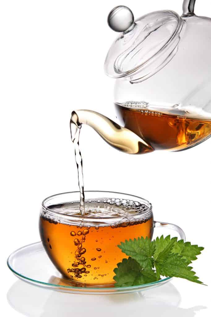 Glass teapot pouring tea into a glass teacup and saucer with a sprig of mint on saucer.  How to make tea guide.