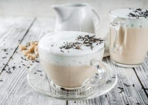 london fog tea latte in a glass cup and saucer with dried lavender flowers sprinkled on top