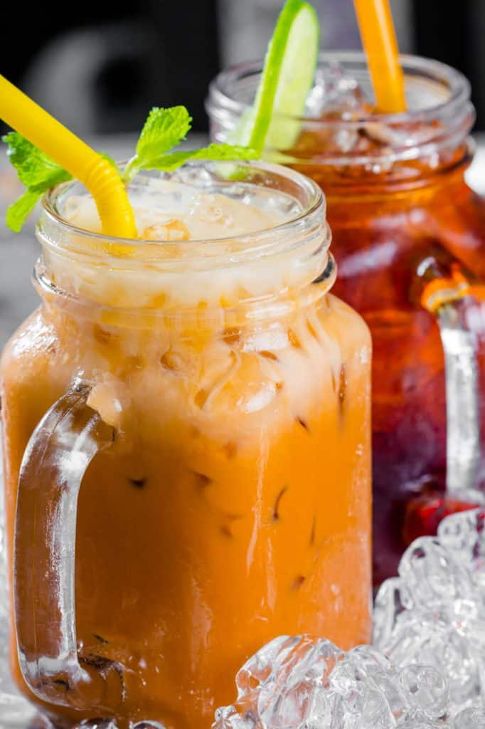 Thai iced tea in mason jars with mint sprigs, lime and yellow straws.