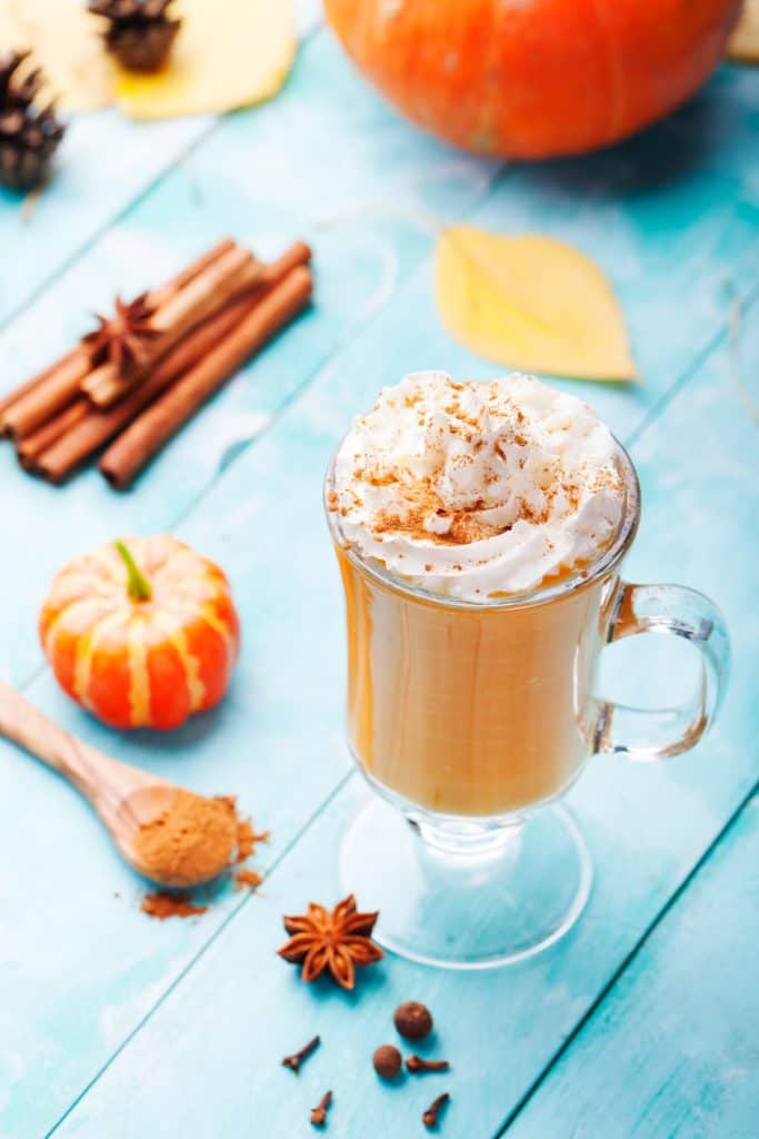 pumpkin spice chai latte on a blue tabletop with spices and miniature pumpkins
