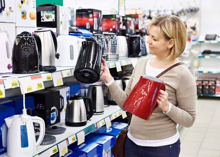 woman choosing the best electric kettle in a department store
