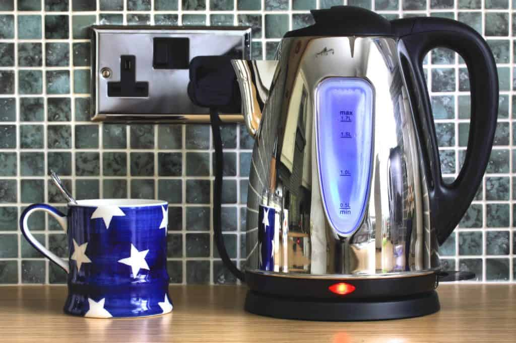 best electric kettle on a countertop with a blue mug and gray backsplash.