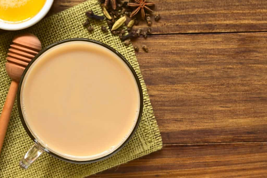 chai tea latte on a green placemat with spices