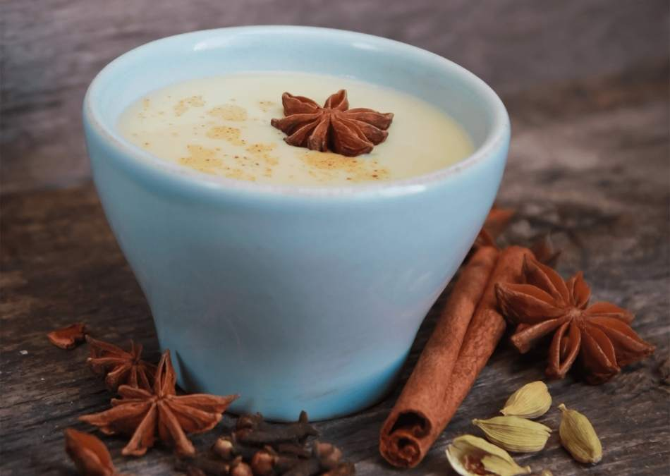 chai tea latte in a white cup with star anise.