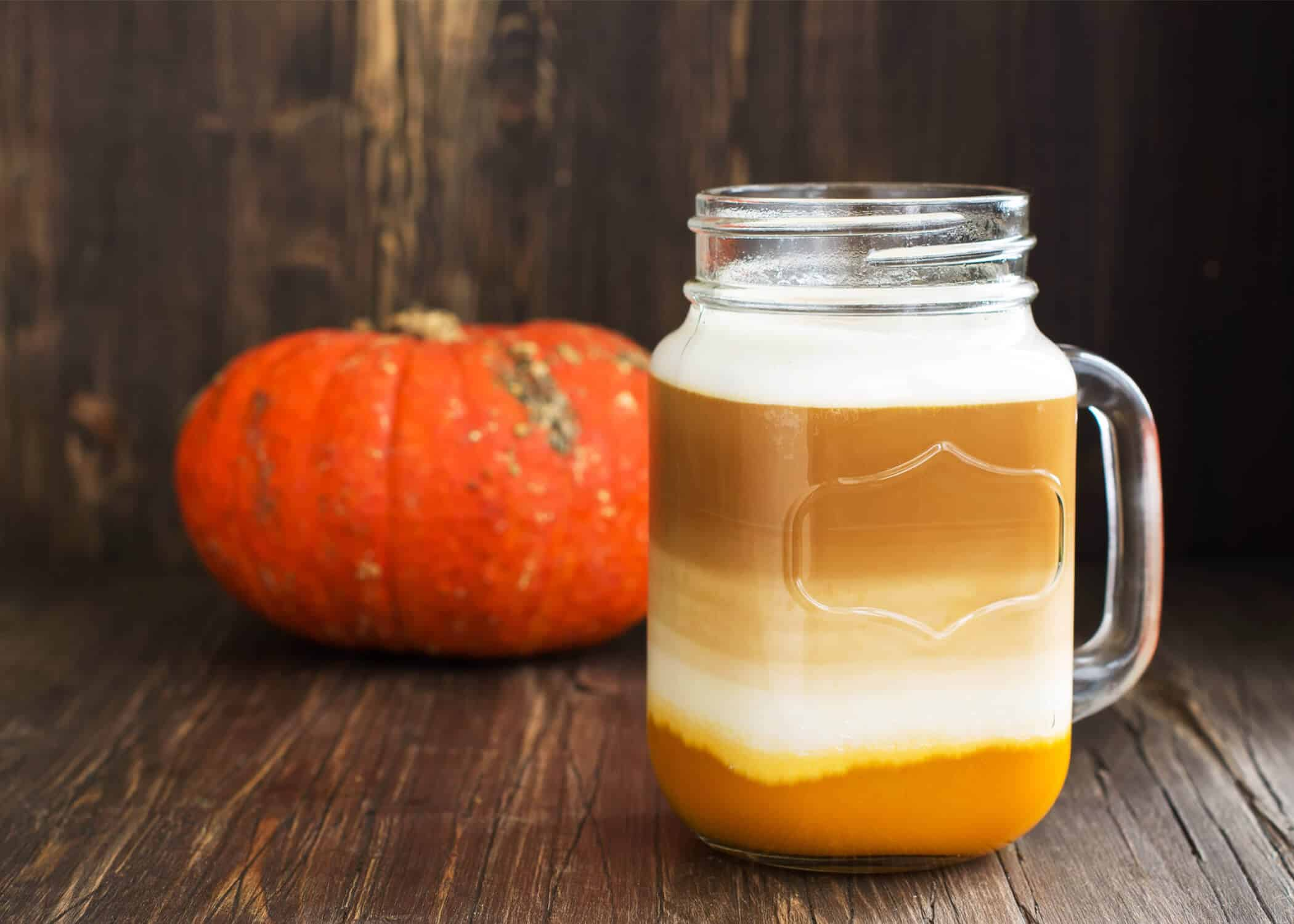 pumpkin spice chai latte with a miniature pumpkin on a wood background