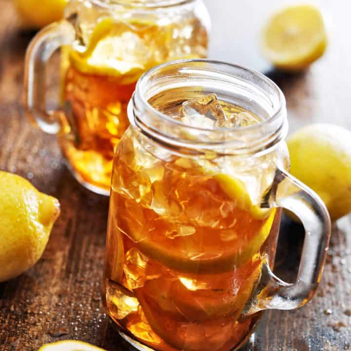 two mason jars filled with sweet tea recipe and lemons