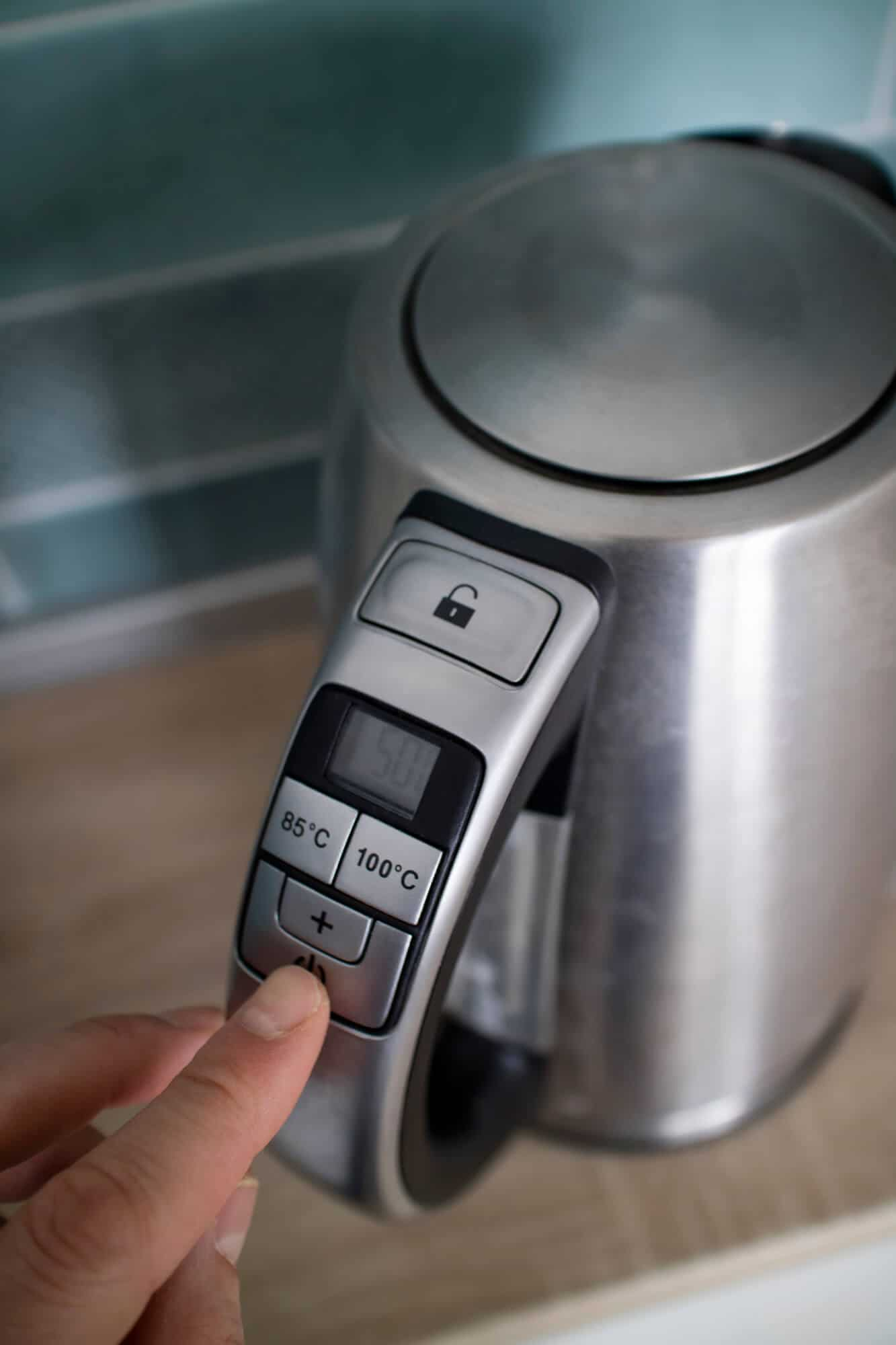 electric kettle on a countertop with temperature control buttons