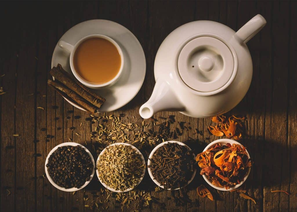 tea accessories with white teapot and white teacup and loose tea on a wooden background