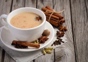 chai tea in a white teacup and saucer with masala spices