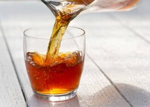 cold brew iced tea being poured from a pitcher into a short glass
