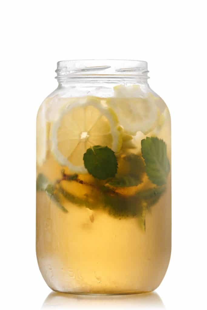 mason jar of cold brew iced tea with mint and lemon slices
