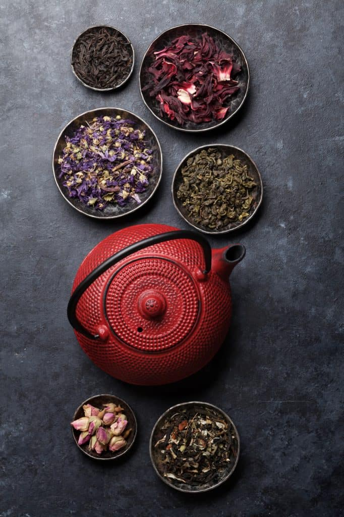 Red iron teapot with saucers of dried teas on a dark slate background