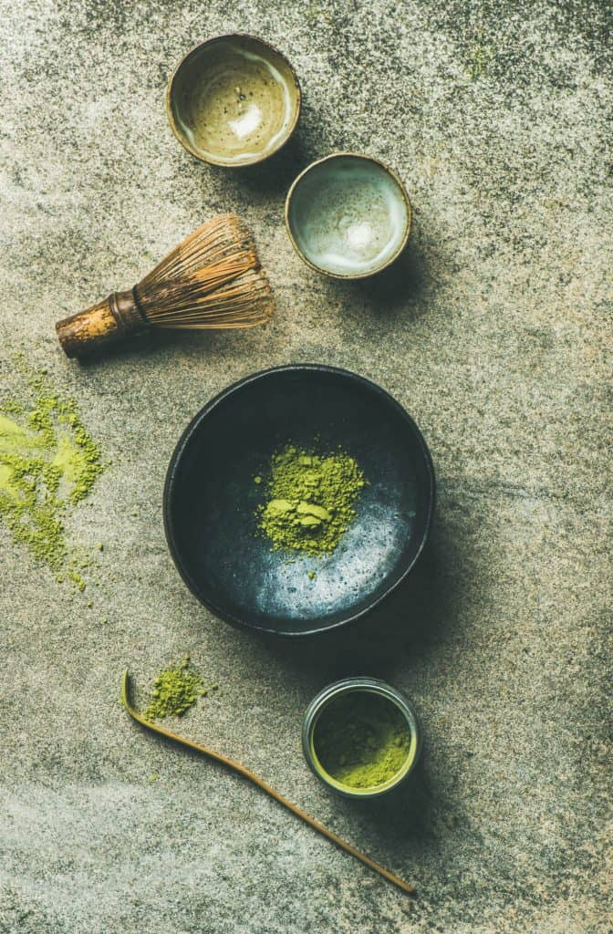 matcha tea in a black bowl with matcha utensils
