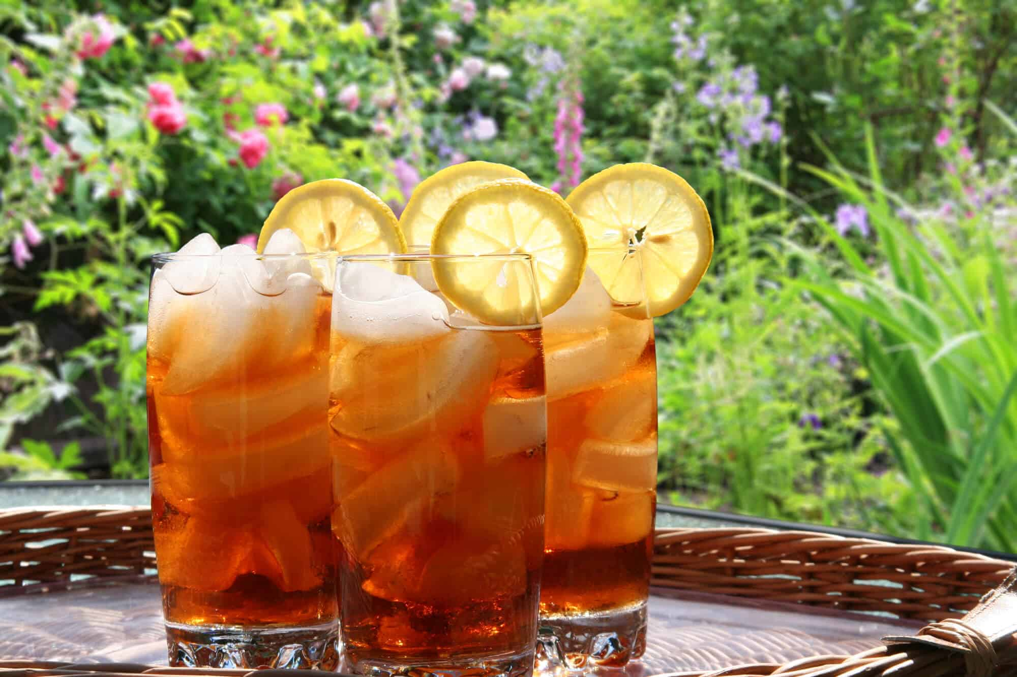 four glasses of iced tea or sweet tea with lemon slices in a garden