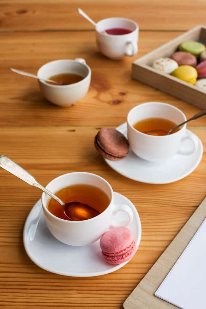 White teacups and saucers on a wood table with macaroons