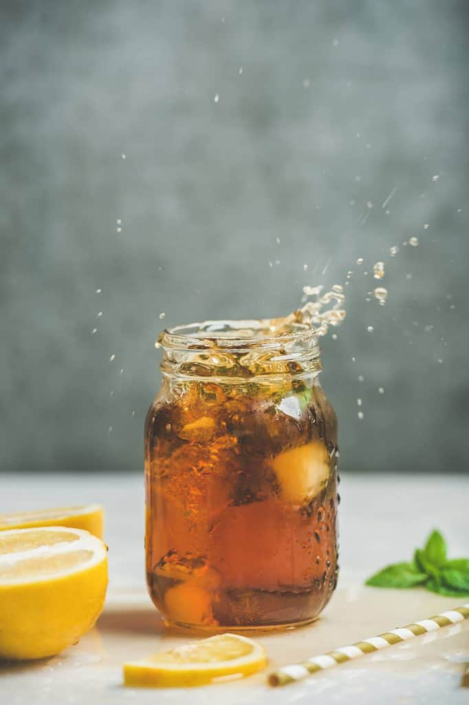 mason jar of cloudy iced tea with lemons and a straw on a table with a green background