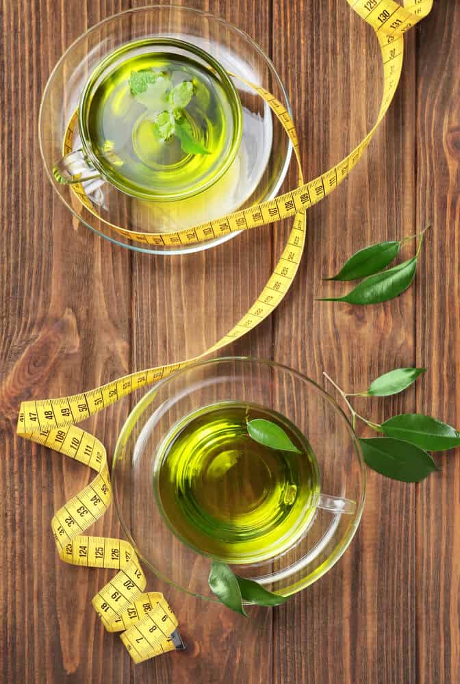 is tea good for weight loss.  a cup of mint tea on a wooden background with a tape measure