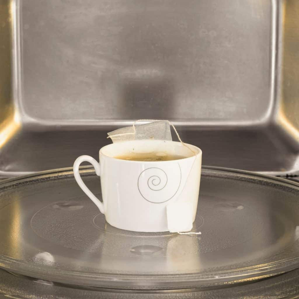 cup of tea with a teabag on the carousel of a microwave. how to make tea in the microwave