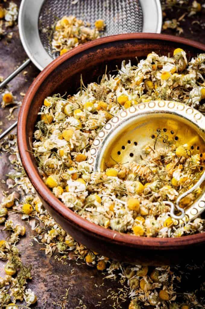 chamomile tea buds in a terra cotta bowl