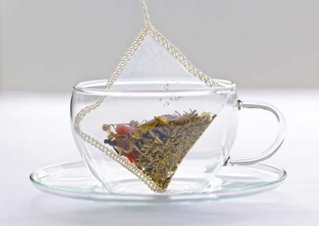 glass teacup with tea bag suspended. who invented the tea bag