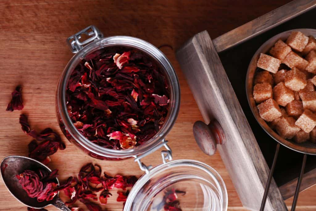 dried hibiscus tea in a glass jar on a wood counter