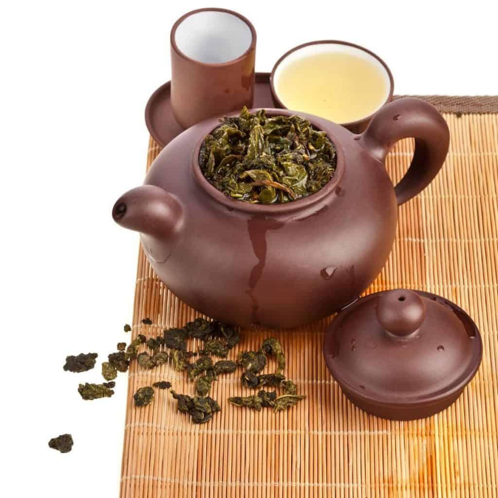 oolong tea in a brown stoneware teapot on a bamboo Matt