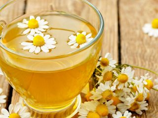 chamomile tea in a glass cup with flower buds on a wooden table