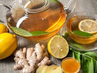 glass teapot with ginger tea and lemons