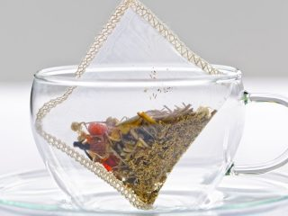 who invented the tea bag photo of a glass teacup and saucer with a tea bag suspended inside