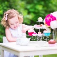 how to host a tea party for kids girl pouring tea in a garden